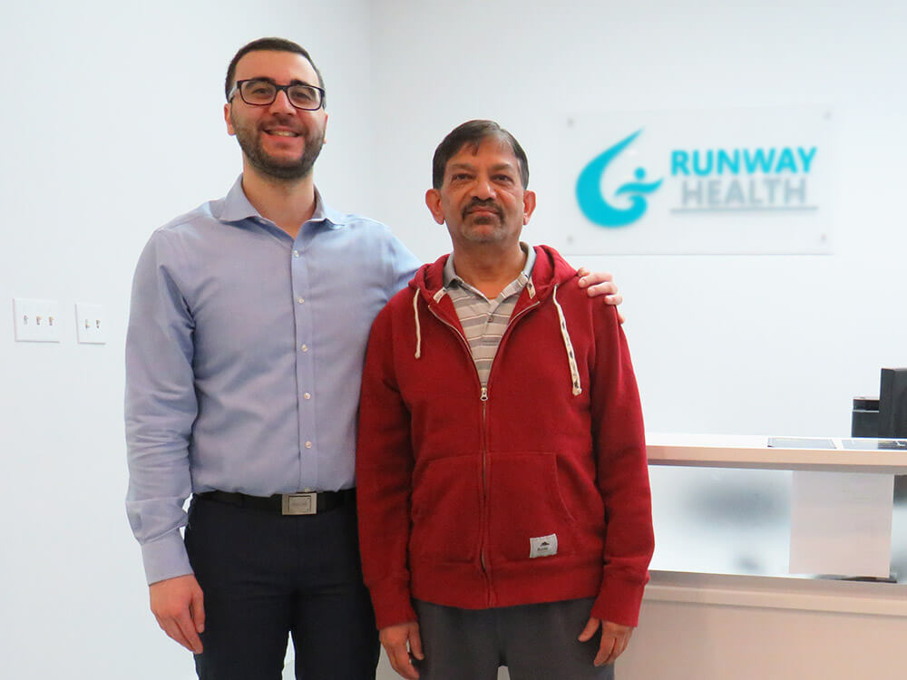 Dr. Omar, a chiropractor, is in reception with Harish, a patient who underwent laser enhanced knee decompression.