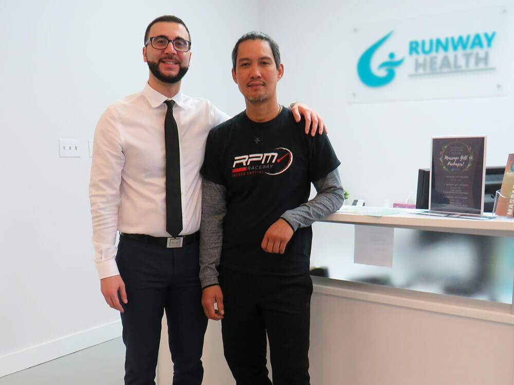 Dr. Omar, a chiropractor, is in reception with James, a long-time patient of the clinic.