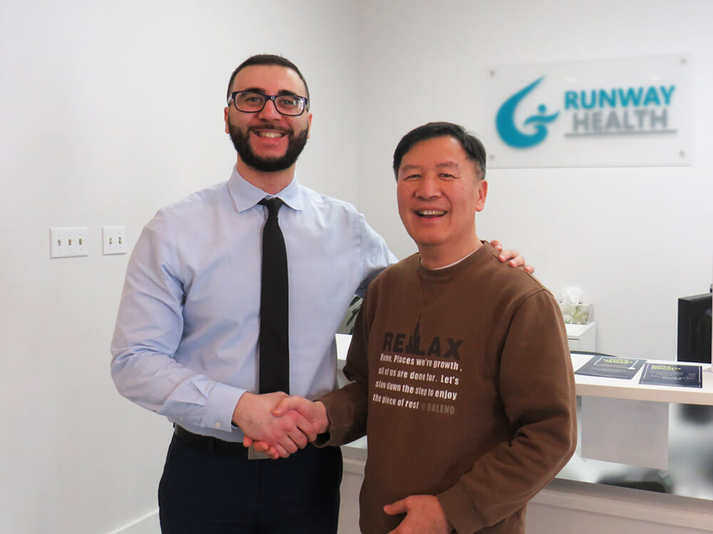 Dr. Omar, a chiropractor, is in reception shaking hands with Raymond, a long-time patient of the clinic.