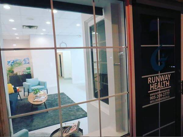 A shot from outside of the clinic looking in through the window and seeing a portion of reception at Runway Health.