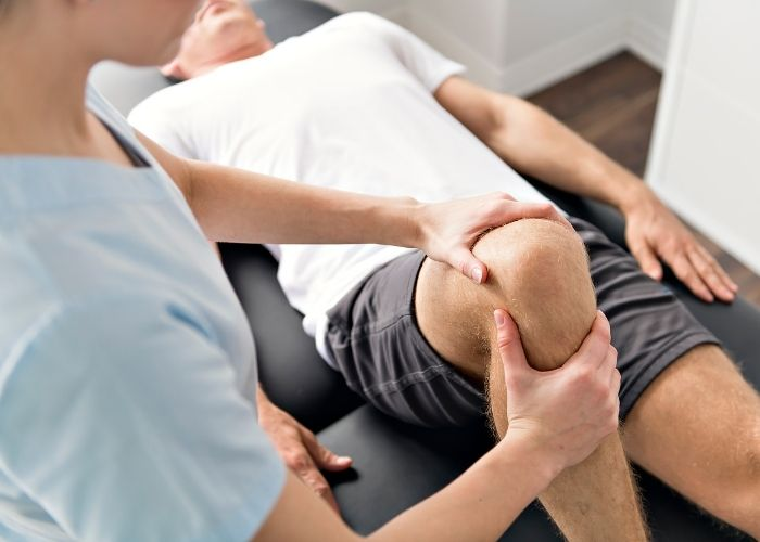 patient in white t-shirt on physio table laying face up with a physiotherapist examinin right knee pain with knee flexed.
