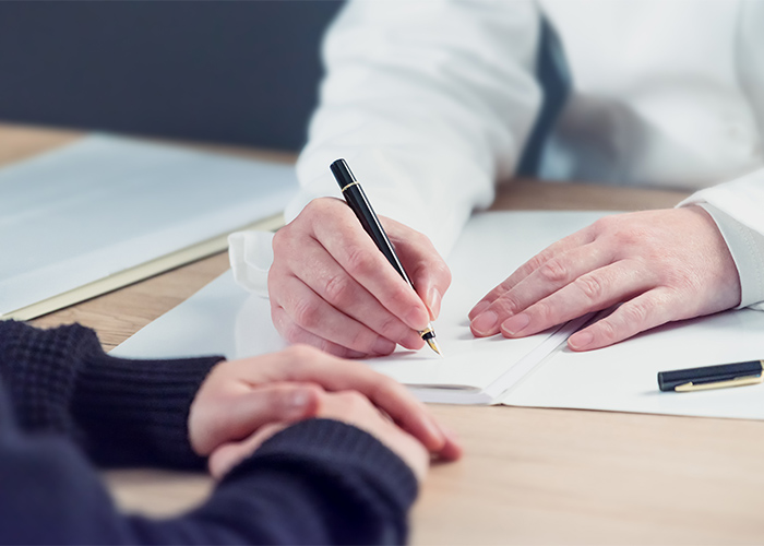 A chiropractor writing down results of a history and examination of a patient who is being assessed and examined for their shoulder and knee pain.
