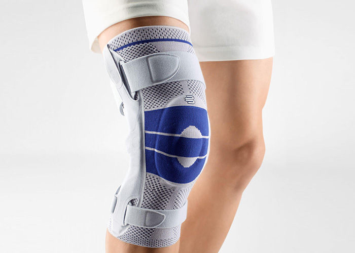 A person standing and wearing a orthoapedic knee brace on their right knee. The brace is a GenuTrain S Model of the brand Bauerfeind which is manufactured in Germany.