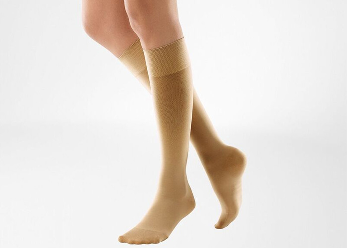 The legs of someone who is wearing beige compression stockings to help increase circulation and relieve tired and fatigued legs.