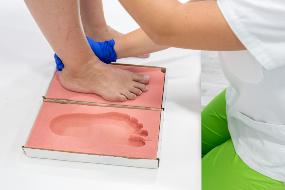A chiropractor performing a orthotics exam of a patient by using a 3D volumetric foam cast to create a mould of the patient's foot to create a custom-made orthotic.