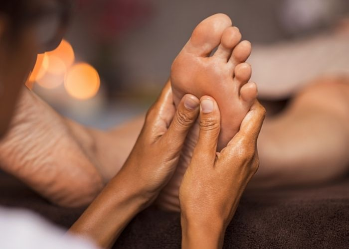 A massage therapist doing trigger point therapy on the sole of the foot of a patient who is laying on their back.
