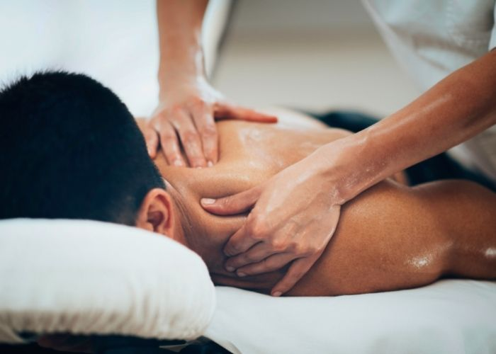 A massage therapist doing deep tissue release on the shoulder of a patient who is laying on their back. This can help circulation, increase range of motion, provide pain relief, and improve posture.