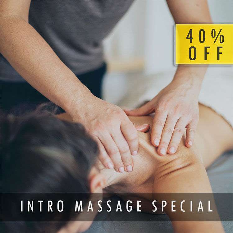 A woman laying on her stomach with a massage therapist doing deep tissue massage to their upper back and shoulder.