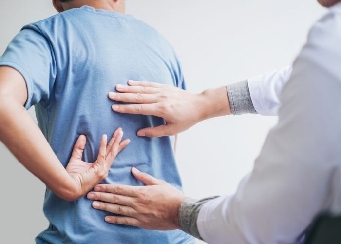 A physiotherapist assessing the lower back of a patient who is pointing to their area of pain while seated.