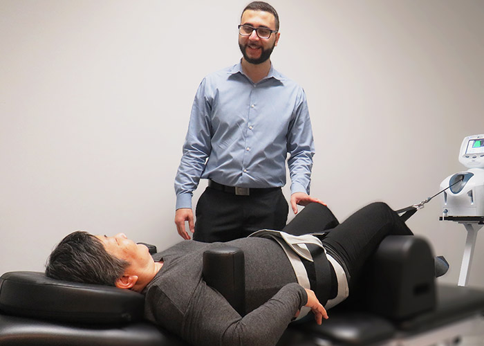 Dr. Omar attending to the side of a patient who is receiving spinal decompression in her lower back to alleviate the pinched nerve and sciatica causes by her disc herniation.