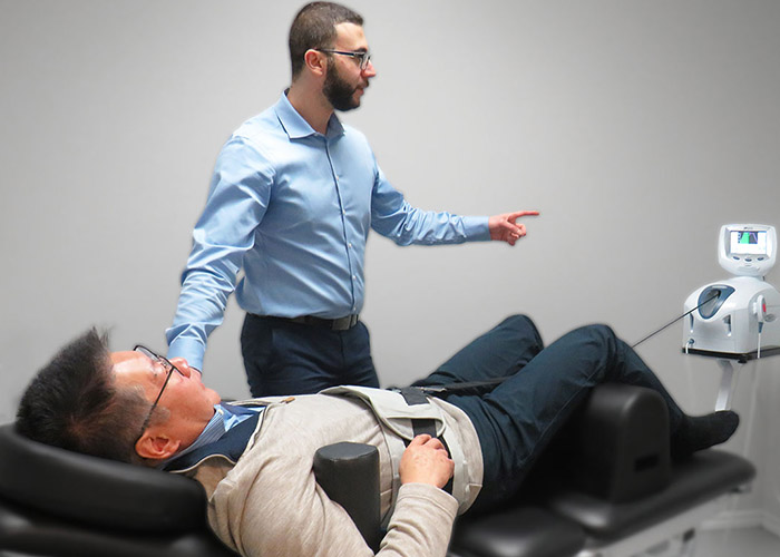 Dr. Omar attending to a patient that is receiving spinal decompression therapy in their lumbar spine to relieve pain in the back and travelling down the leg due to a lumbar disc herniation.