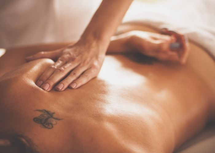 A massage therapist performing a sports massage on a patient laying on their back. The massage therapist is getting deep into the underside of the shoulder blade of the patient.