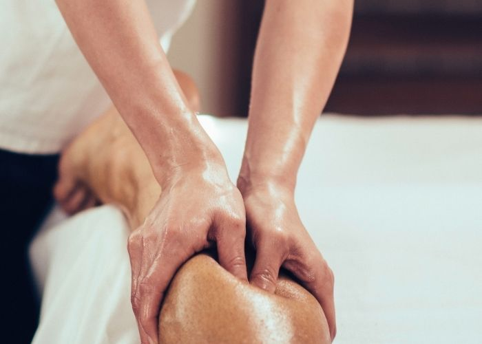 A massage therapist doing deep tissue massge release of the the calves of a patient who is laying on their stomach. Deep tissue massage is a very common form of massage for pain relief and release of stiffness and tightness in the muscles.