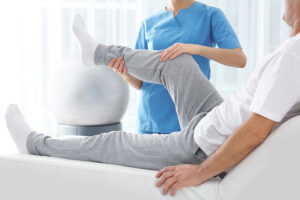 Doctor wearing a blue shirt, holding a patients knee with both hands during physiotherapy appointment