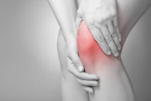 Black and white photo of person holding her knee with pain. The knee is painful and inflammed.