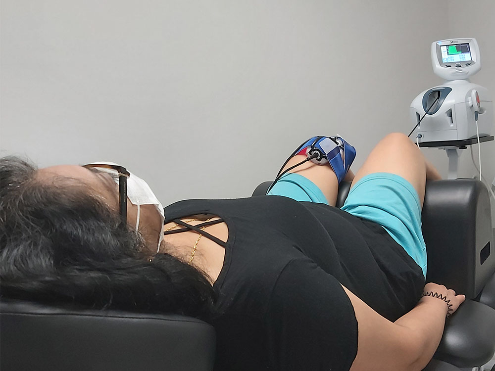 Woman with black shirt and blue shorts laying on physiotherapy bed