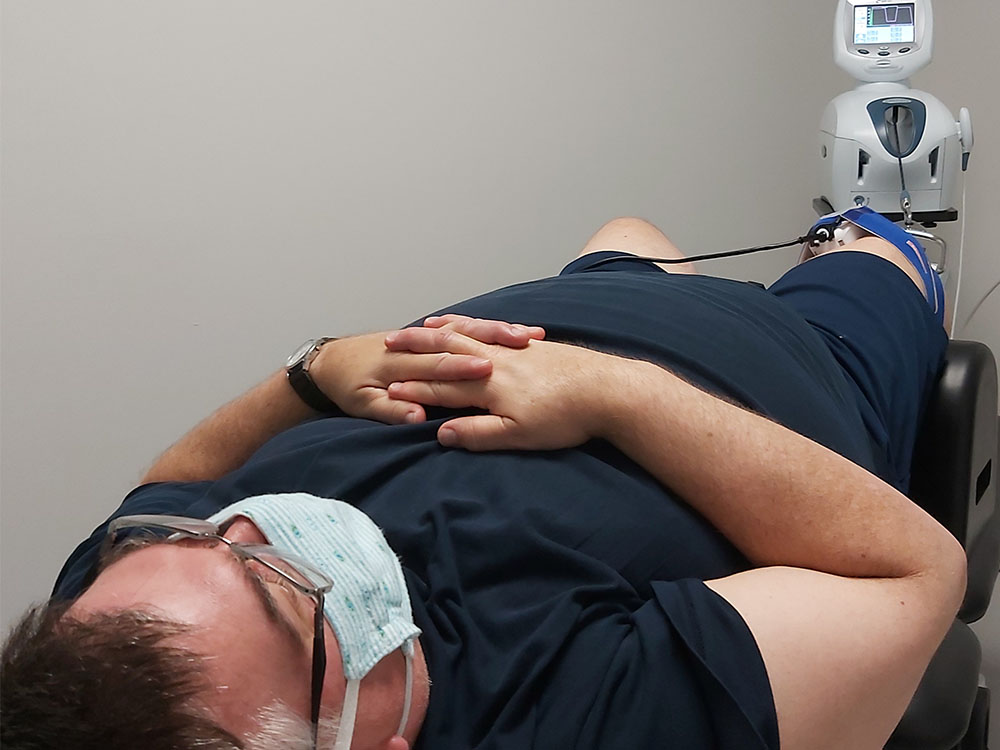 Man laying down on chiropractic bed with his hands across chest strapped in with a blue knee sensor