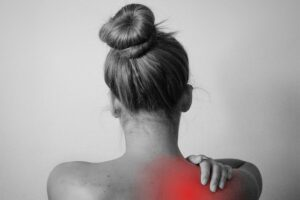 Person holding her shoulder with a red area marking the painful area