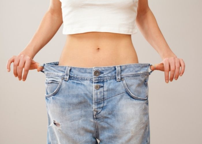 Woman in a white crop top and holding oversized jeans that don't fit her